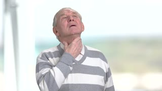 Old coughing man, blurred background. Senior man having sore throat and cough. Cold and illness concept.