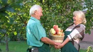Old couple and apple basket. Smiling people in aprons. Spring has come.