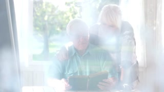 Old couple with a book. Serious man and woman. The war diary.
