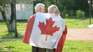 Old couple wrapped in flag. Two people walking, back view. Life in immigration.