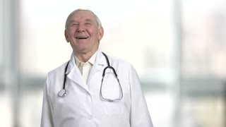 Old doctor laughing and putting hands up. Aged friendly physician bright, blurred windows in hospital background.