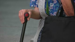 Old grandma with a cane stick. Close up. Hands of old senior lady with stick.