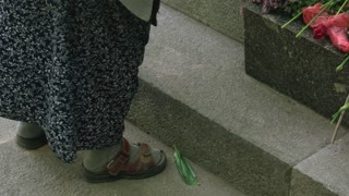 Old lady feet. Put flwoers on memorial stone.
