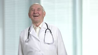 Old male doctor laugh at your jokes. Blurred windows with louvers background.