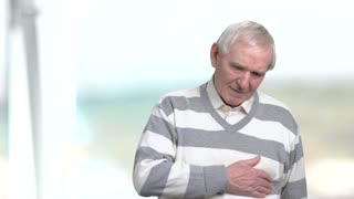 Old man feeling pain in his chest. Senior man having heart problems, blurred background.