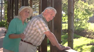 Old man has backache. Elderly couple outdoors. Pains in lower back. Old traumas influence health.