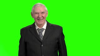 Old man in black suit laughing hard, slow-motion. Grandpa laughing out loud against green hromakey background.
