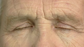 Old man is opening his eyes close up. Wrinkled face of elderly man close up. Older man closed eyes close up.
