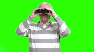Old man looking through binocular. Grandpa with binocular, green hroma background.