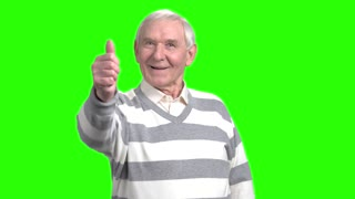 Old man showing thumb up. Smiling cheerful grandpa shows thumb up, green hromakey background.