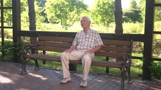 Old man sitting on bench. Elderly guy with thoughtful face. Things used to be different. Lots of thoughts about past.