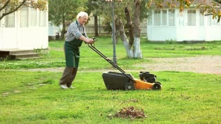 Old man with lawn mower. Senior gardener in apron. How to choose gardening equipment.