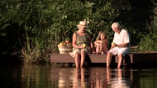 Old people and grandchild with picnic basket. Grandparents and granddaughter sitting near water with basket full of fruits. Upset girl at lake.