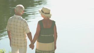 Old people holding hands. Couple of seniors standing near water in sunny day. Love that lasts a lifetime.