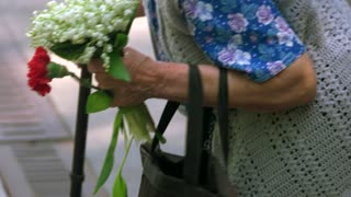 Old senior grandma with flowers during memorial day. Close up. Very old lady with stick, flowers and bag.