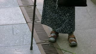 Old senior lady walking with stick. Close up feetof grandma.