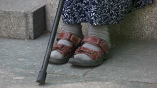 Old senior poor lady with stick. Legs feet close up.