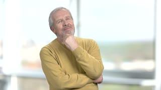 Old thinking man, blurred background. Mature man looking pensive on blurred background. Portrait of handsome senior man.