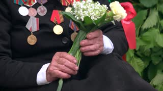 Old war veteran with flowers and medals. 9 may, victory day. Close up.
