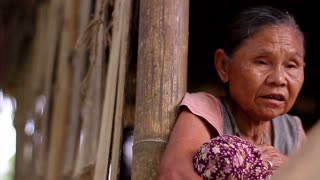 Old woman from the slums. Old grandmother in a bamboo house. Hands of an old woman. Wrinkled hands. Wrinkled face.
