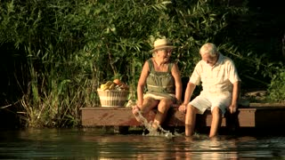 Old woman kissing man near water. Couple of seniors sitting near river and dangling with legs in water. Romantic rest of elderly people.