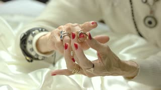 Old woman putting on ring on finger. Elderly woman with well-groomed manicured hands wearing many rings on fingers. Aristocratism and wealth concept.