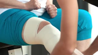Older woman with injured leg. Male hands bandaging senior womans leg at gym close up. How to reduce muscles sprain.