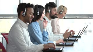 Operators with headsets in bright office. Side view of smiling coworkers sit by the table in headphones.