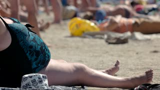Overweight woman in swimsuit. Obese lady sitting on beach. Poor nutrition harms health. Obesity is a widespread problem.