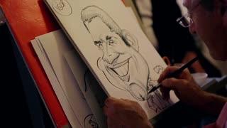 Painter paints a caricature on the paper. The artist paints a person's face.