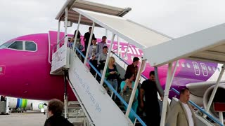 Passengers leaving the gangway of the plane. People at the airport.