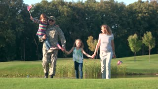Patriotical american family with backgrounds proud of US army. Soldier wife and kids moving together in the park.
