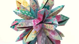 Patterned origami flower on white background. Amazing design of handmade paper flower decoration. Kusudama art concept.