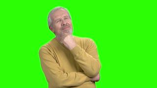 Pensive mature man on green screen. Elderly man thinking on chroma key background.