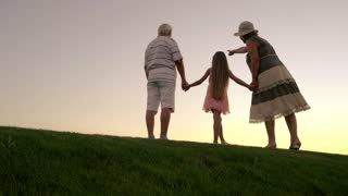People enjoying sunset sky outdoors. Grandparents with granddaughter holding hands on evening nature background. Look into the future.