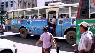 People hurry to bus in Myanmar.
