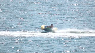 People on flying banana boat. Inflatable boat ride, slow-mo.