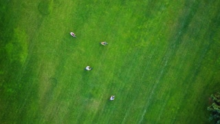 People riding a bikes, aerial view. Group of friends cycling on green lawn, aerial drone view. Healthy lifestyle concept.