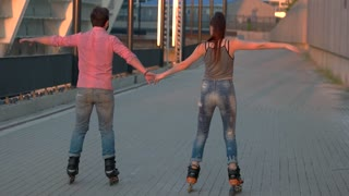 People rollerblading and holding hands. Back view of a couple. Idea for active date. Romance and sport.
