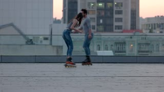 People rollerblading in the city. Couple smiling and laughing outdoor. Try to catch me. Fast and agile.