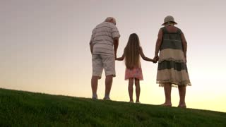 People standing on sunset background. Girl with grandparents holding hands on green grass. Happy family summer vacation on green meadow.