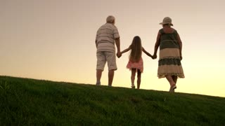 People walking on evening sky background. Girl and grandparents holding hands and walking beyond horizon. Leave the past behind.