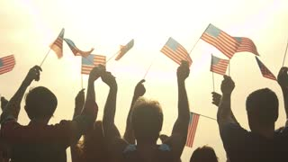 People with American flags at morning sky background. Patriots celebrating the Fourth of July. Independence Day concept.