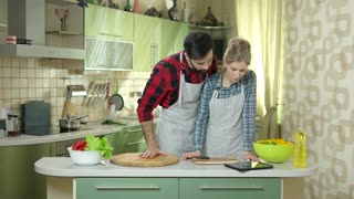 People with tablet in kitchen. Woman and man preparing food. Home cooking blogs.