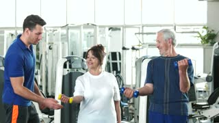 Personal trainer helping lift dumbbells to seniors. Happy senior couple lifting dumbbells while male instructor guiding them. Easy strength training workouts.
