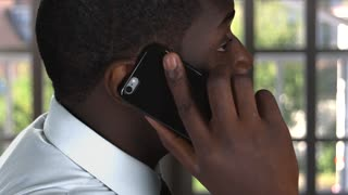 Phone talk of black man. Guy with cellphone indoors. Whom to trust.