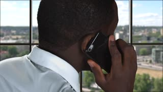 Phone talking on city backdrop. Afro-american guy with cellphone. Rescue the business.