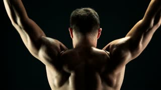 Physique big arms workout. Young fit man working out with heavy equipment, back view. Men muscular back.