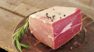Piece of frozen beef. Meat on old wooden plate. Rustic cooking traditions.