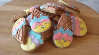 Pile of cookies with icing on wooden board. Colorful decorated cookies in a shape of ice cream. Healthy sweets for kids.